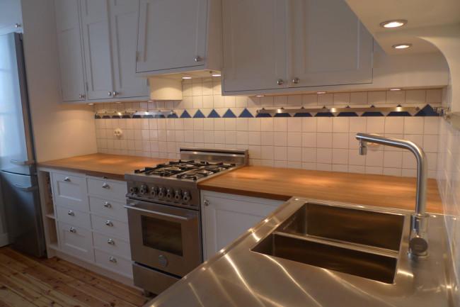 Platsbyggd köksinredning med infällda luckor och lådor.