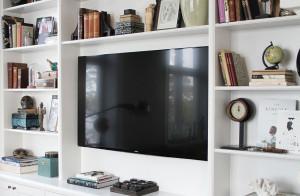 Platsbyggd hylla runt TV i vardagsrummet